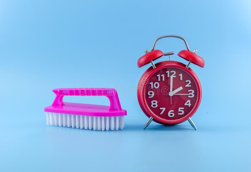 O plástico esfrega a escova com o despertador vermelho no fundo azul imagens de stock royalty free