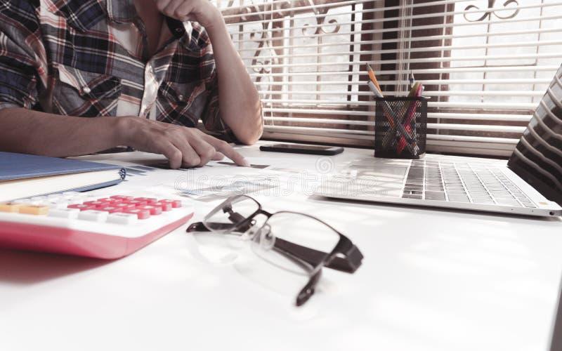 O planeamento de trabalho da lista de verificação do homem de negócios investiga na tabela fotos de stock