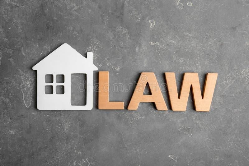 O plano bonito coloca a composição com palavra LEI e modelo da casa no fundo cinzento fotografia de stock royalty free