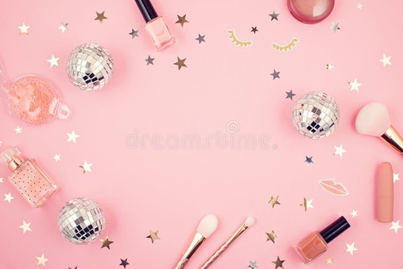 O plano coloca com os acessórios das meninas do encanto sobre o fundo cor-de-rosa foto de stock