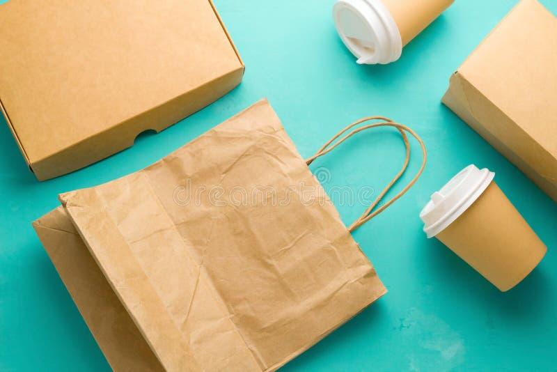 O plano coloca os tipos de papel recicláveis que empacotam em um fundo azul, saco de papel, vidro descartável, caixa de cartão fotos de stock royalty free