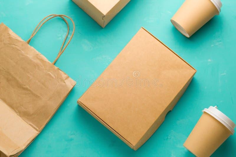 O plano coloca os tipos de papel recicláveis que empacotam em um fundo azul, saco de papel, vidro descartável, caixa de cartão imagens de stock