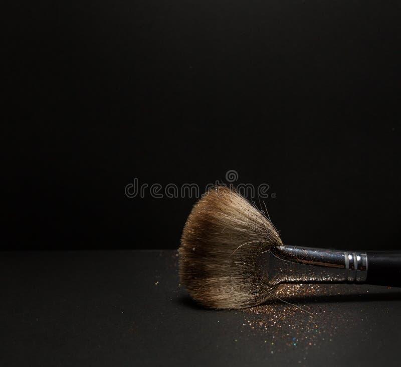 O plano cora escova com cora nele, pó fraco e o brilho cora, no fundo preto imagens de stock royalty free