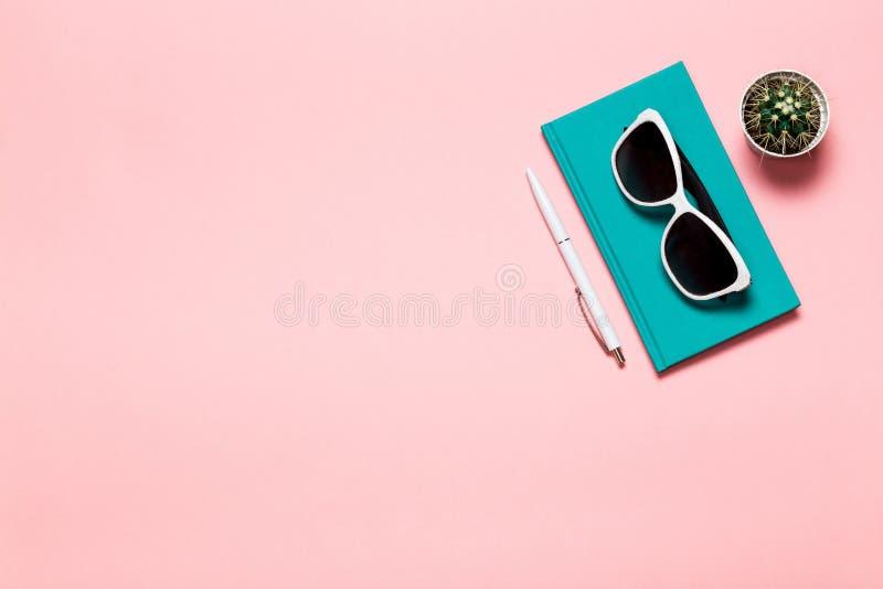 O plano criativo coloca a foto da mesa do espaço de trabalho com caderno de água-marinha, monóculos, cacto com fundo do rosa do e imagens de stock
