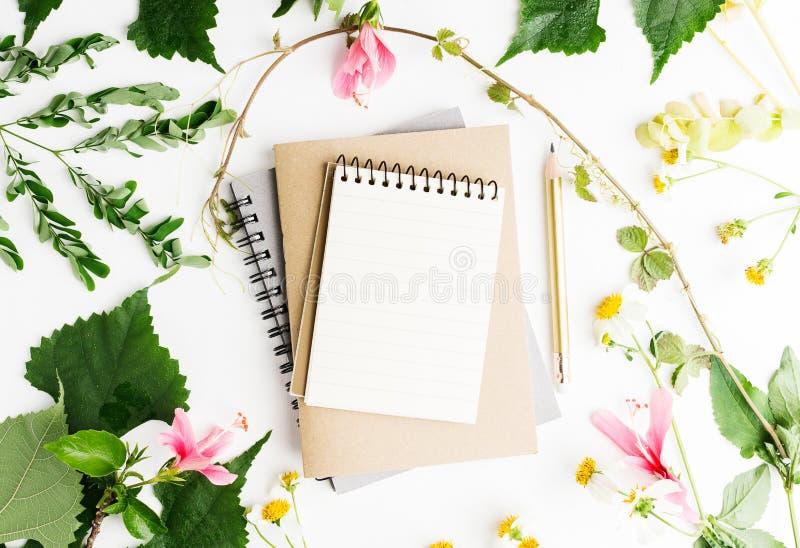O plano da vista superior coloca o livro de nota vazio com o modelo das folhas do verão e das flores da margarida fotografia de stock royalty free