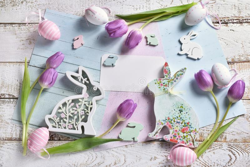 O plano de easter da cor pastel coloca com tulipas e coelhos foto de stock royalty free