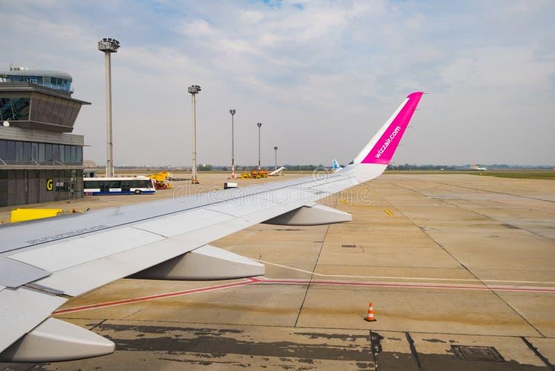 O plano de Wizzair aterrou o no aeroporto de Bratislava, vista à asa do avião fora da janela da vigia fotografia de stock