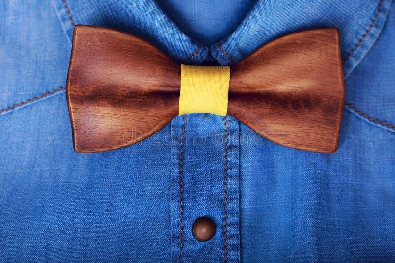 O plano do close up coloca a camisa ocasional da calças de ganga dos homens com laço amarelo de madeira Acessórios do homem Fundo imagem de stock royalty free