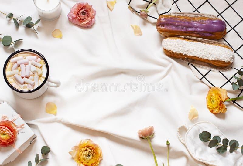O plano do conceito coloca com flores, uma xícara de café, os eclairs e as folhas na cobertura branca imagens de stock