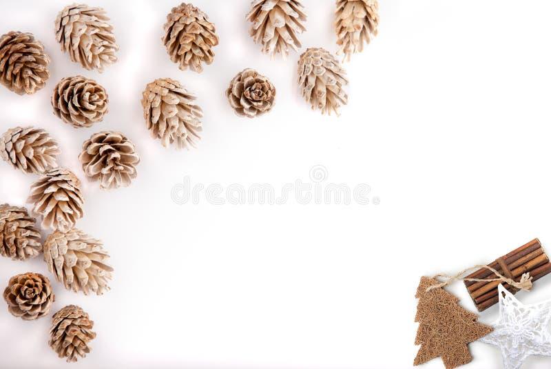 O plano do Natal coloca o desktop do modelo, cones do pinho em um fundo branco fotos de stock