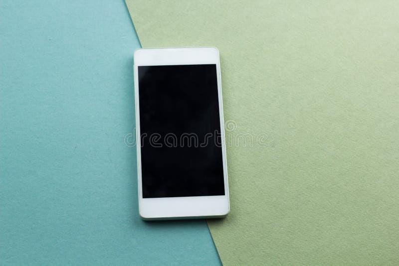 o plano do smartphone coloca em um fundo verde e azul fotos de stock