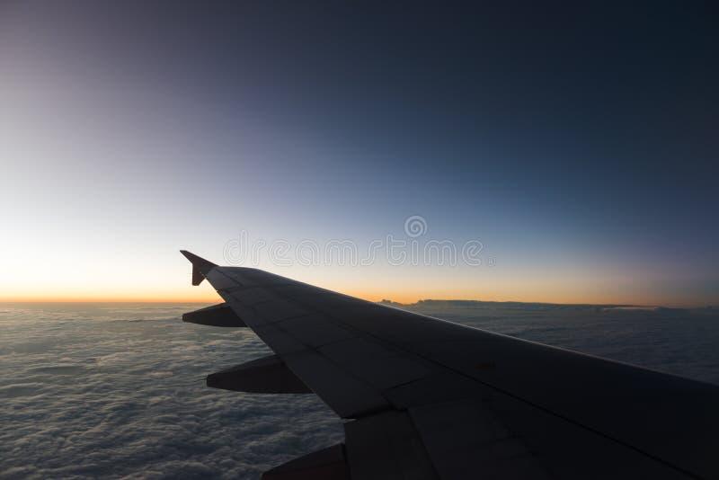 O plano está voando através do céu do por do sol foto de stock royalty free