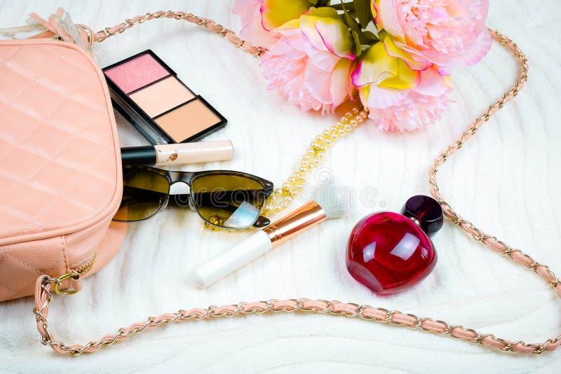 O plano fêmea coloca com óculos de sol e parfume do saco Fundo branco foto de stock royalty free