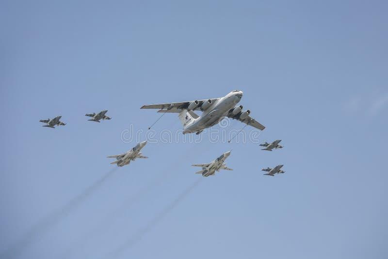 o Plano-petroleiro Il-78, acompanhado de 2 bombardeiros su-24 e de 4 Yak-130 no céu na parada da vitória em Moscou imagem de stock
