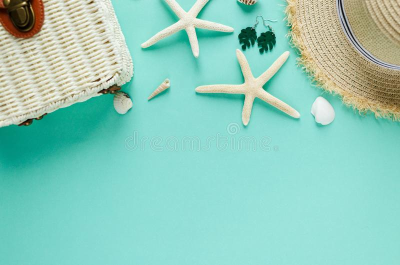O plano tropico coloca com chapéu de palha, saco, estrela do mar, escudos, óculos de sol, barco, brincos no fundo verde Configura foto de stock