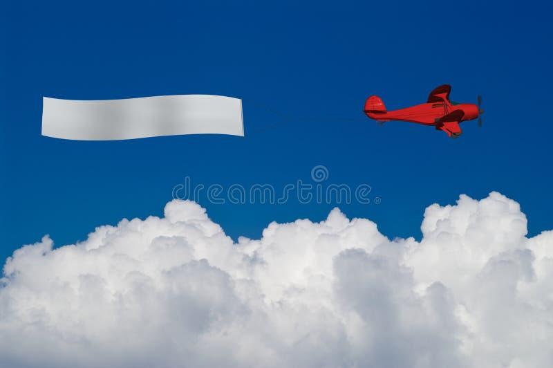 O plano vermelho puxa a bandeira em branco acima das nuvens brancas ilustração stock