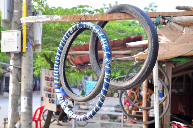O pneu de carro é pendurado sobre para observar um sinal da estação do reparo do carro em Vietname fotografia de stock