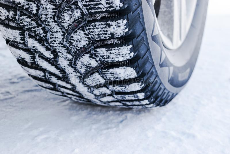 O pneu de carro no fim da neve acima Trilhas do carro na neve Traços do carro na neve Pneus do inverno Pneumáticos cobertos com a imagem de stock royalty free