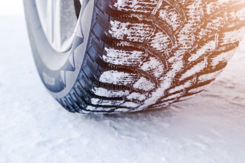 O pneu de carro no fim da neve acima Trilhas do carro na neve Traços do carro na neve Pneus do inverno Pneumáticos cobertos com a imagens de stock royalty free