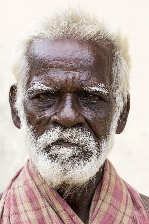 O pobre homem indiano idoso com um marrom escuro enrugou o cabelo do cara e o branco e uma barba branca, sério ou triste fotos de stock royalty free