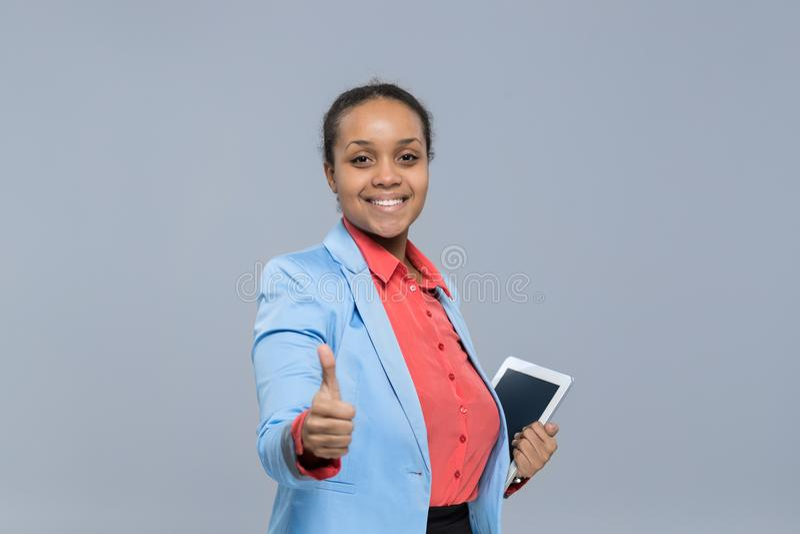 O polegar afro-americano da menina do tablet pc novo da posse da mulher de negócio aprova acima fotos de stock royalty free