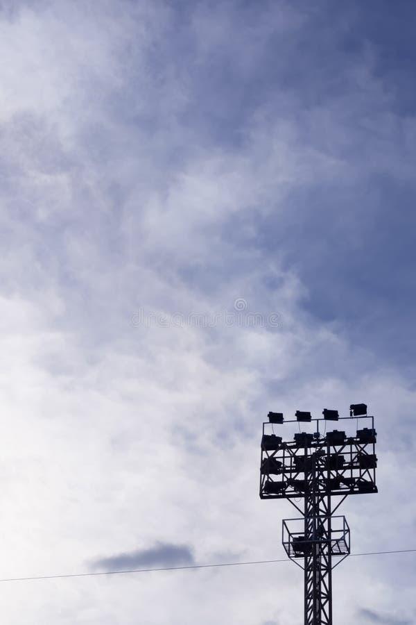 O polo claro do projetor com fundo com nuvens, silhueta do céu imagem de stock