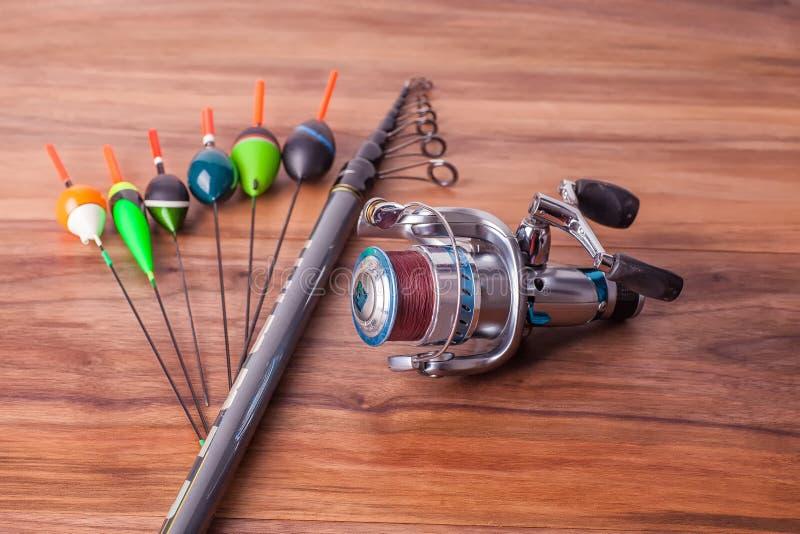 O polo de pesca com anéis e o carretel, flutuadores encontram-se em placas americanas da noz fotografia de stock royalty free