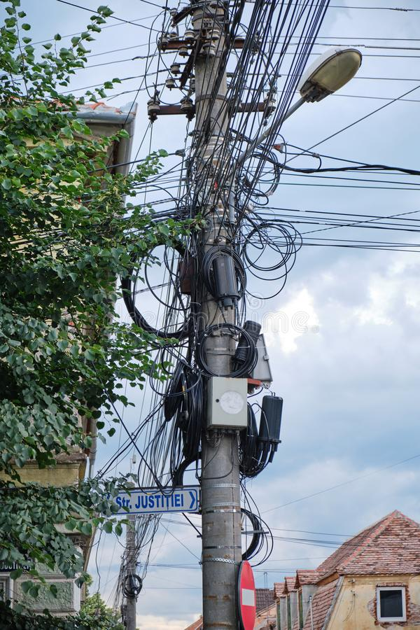 O polo de rua com TV, internet, telefonia e cabos de eletricidade pendurados nele em uma questão não organizada fotografia de stock royalty free