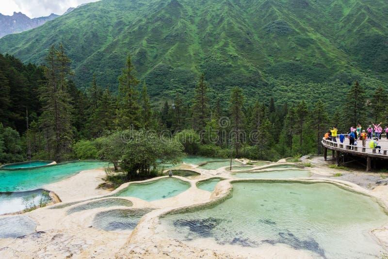 O ponto cênico com os viajantes em convidados dá boas-vindas à lagoa no parque de Huanglong fotos de stock royalty free