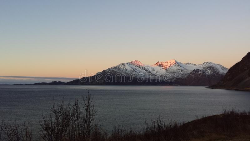 O por do sol alaranjado bonito sobre o fiorde azul poderoso e a montanha ajardinam em Noruega do norte imagem de stock