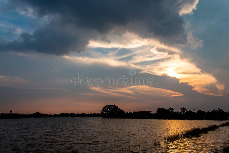O por do sol atrás das reflexões das árvores na água fotografia de stock royalty free