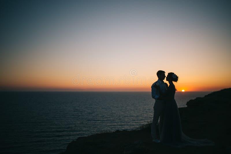 O por do sol bonito no mar, um homem e uma mulher guardam as mãos, olhar em se, um amor fotos de stock