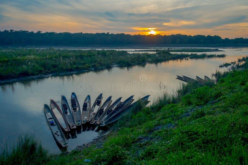 O por do sol bonito no parque nacional de Chitwan, com alguns barcos em seguido no rio, lugar bonito dos yhis é coberto principal foto de stock