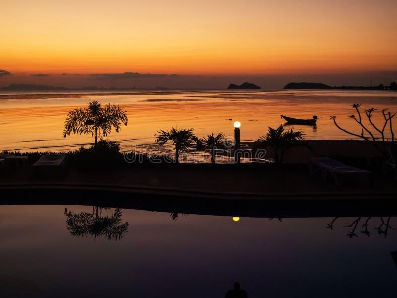 O por do sol com um barco e as palmeiras refletiu na associa??o imagem de stock