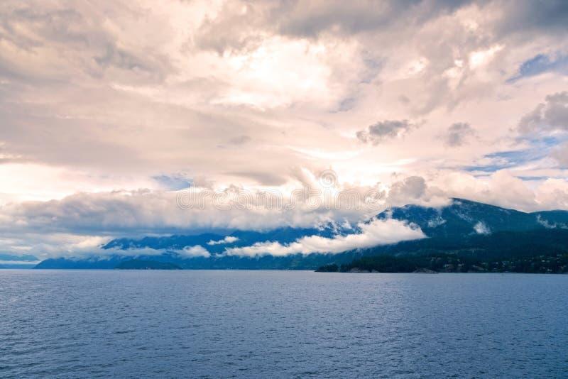 O por do sol dramático colore montanhas da costa de Howe Sound BC Canadá do céu nebuloso foto de stock