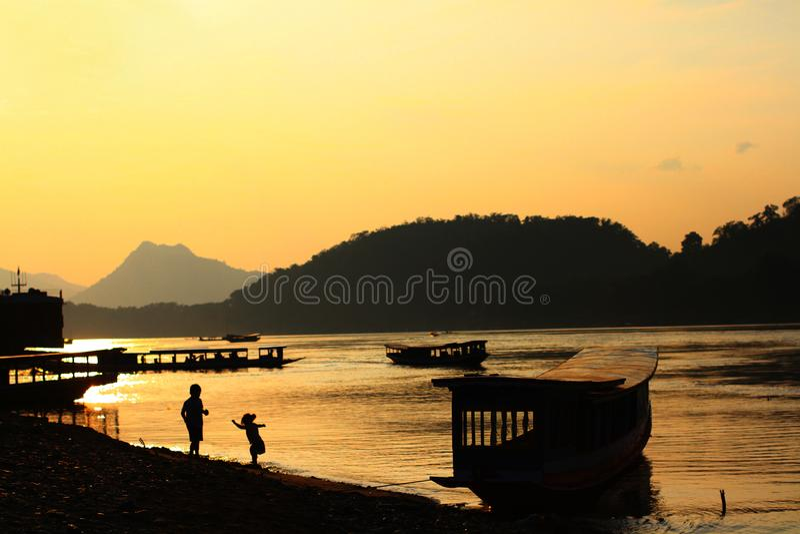 O por do sol e as crianças bonitos no rio imagens de stock