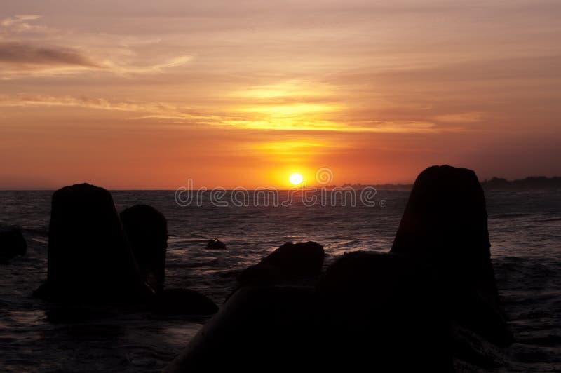 O por do sol e os quebra-mares em Glagah encalham, Yogyakarta, Indonésia imagens de stock royalty free