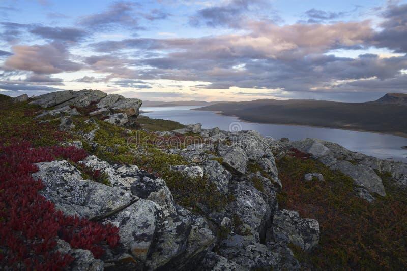 O por do sol impressionante sobre o lago e o rio ajardinam com rocha e primeiro plano vermelho da vegetação fotos de stock