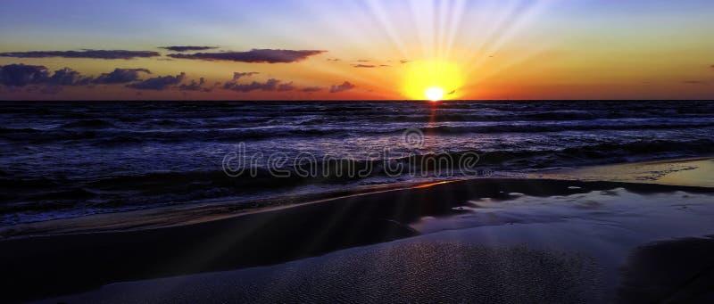 O por do sol na costa polonesa com sol visível irradia - o mar Báltico em Lubiatowo, Pomorskie, Polônia imagem de stock