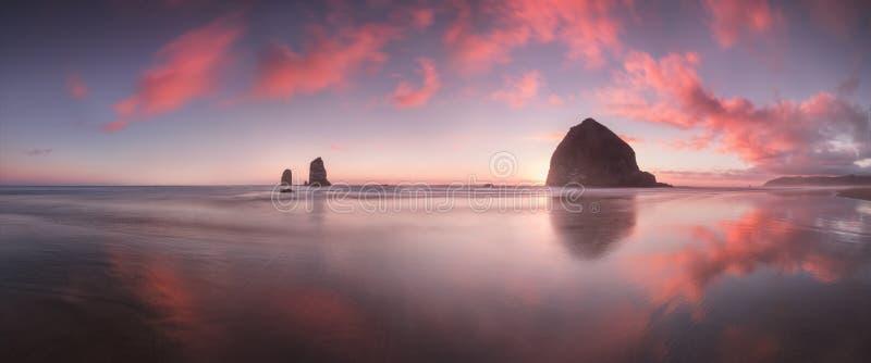 O por do sol na praia do canhão com nuvens dramáticas no fundo e em uma reflexão agradável na água Seascape litoral dramático fotografia de stock