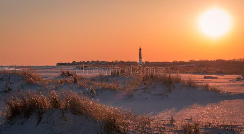 O por do sol na praia como o farol de Cape May está no fundo na ponta do extremo sul de NJ imagens de stock royalty free
