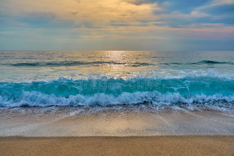 O por do sol na praia tropical, sol atrás das nuvens reflete na água fotos de stock