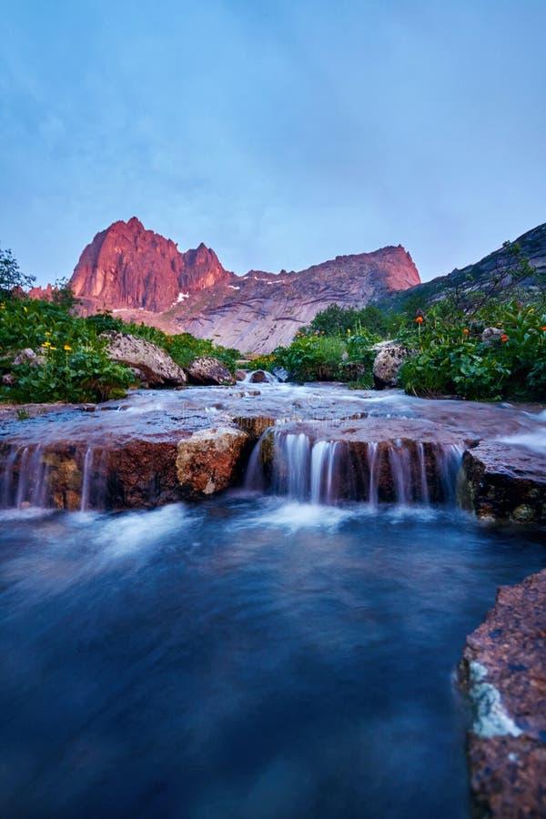 O por do sol nas montanhas aproxima o rio Luz solar refletida em partes superiores da montanha A luz dourada do céu refletiu em u imagem de stock