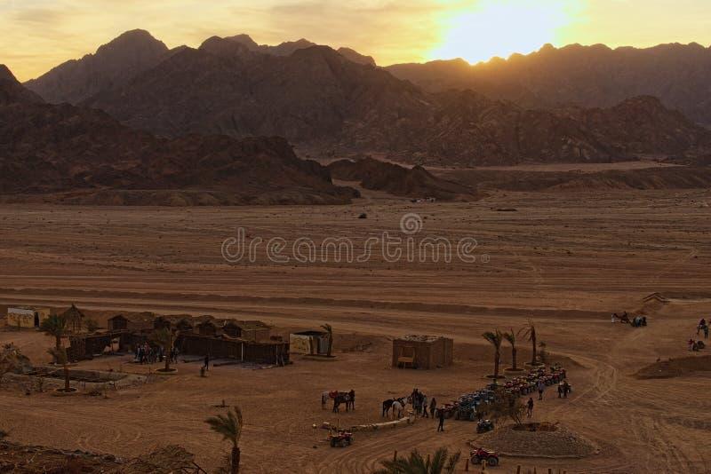 O por do sol nas montanhas do deserto aproxima a vila beduína em Egito foto de stock royalty free