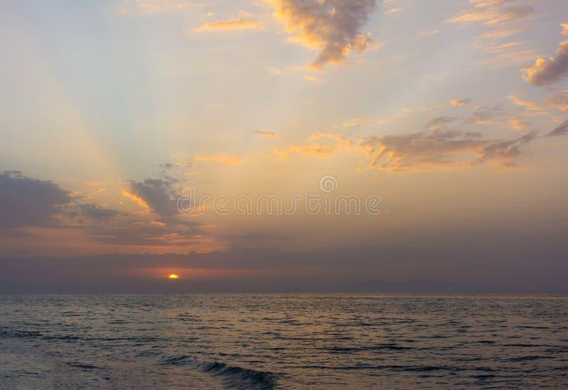 O por do sol no mar, o sol ajusta-se sobre o horizonte, seascape fotos de stock royalty free