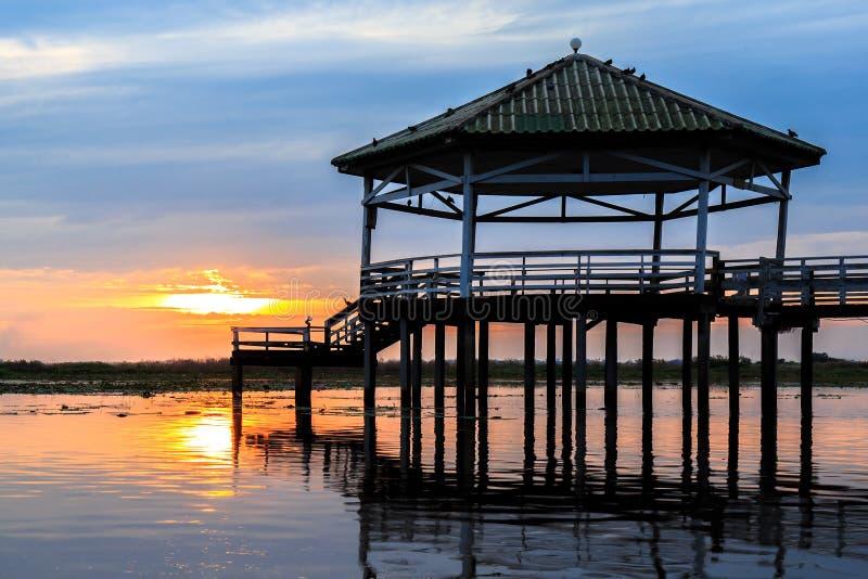 O por do sol no pavilhão no lago ou na lagoa ou o pântano de Bueng consideram Fai, Phichit, Tailândia foto de stock