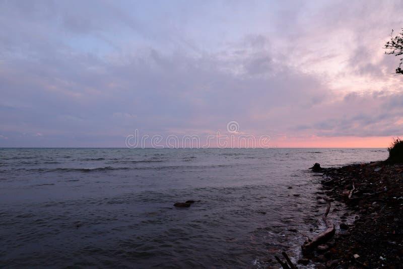 O por do sol, os raios do ` s do sol faz sua maneira através das nuvens pesadas e ilumina o verão, mar incomodado foto de stock