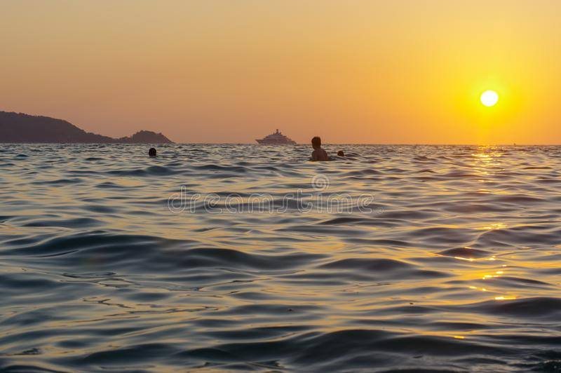 O por do sol romântico bonito cênico sobre o mar com a silhueta dos povos em estar na água e aprecia a laranja da noite imagem de stock royalty free