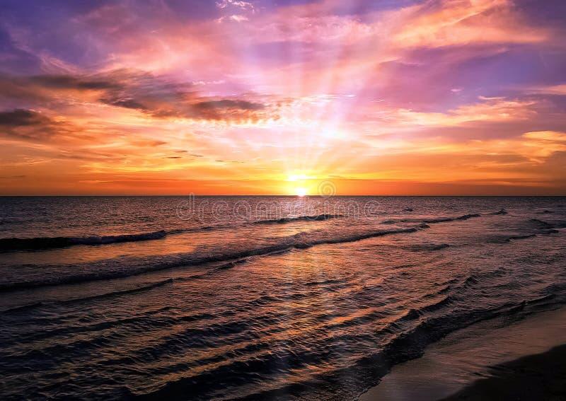 O por do sol sobre a praia cubana com sol visível irradia foto de stock