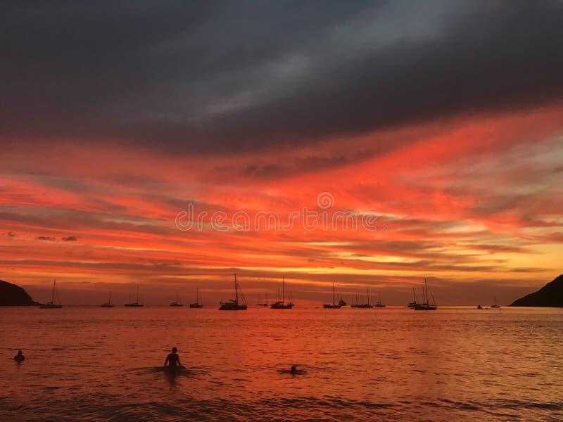 O por do sol vermelho de surpresa da queimadura na praia com povos est? nadando imagens de stock